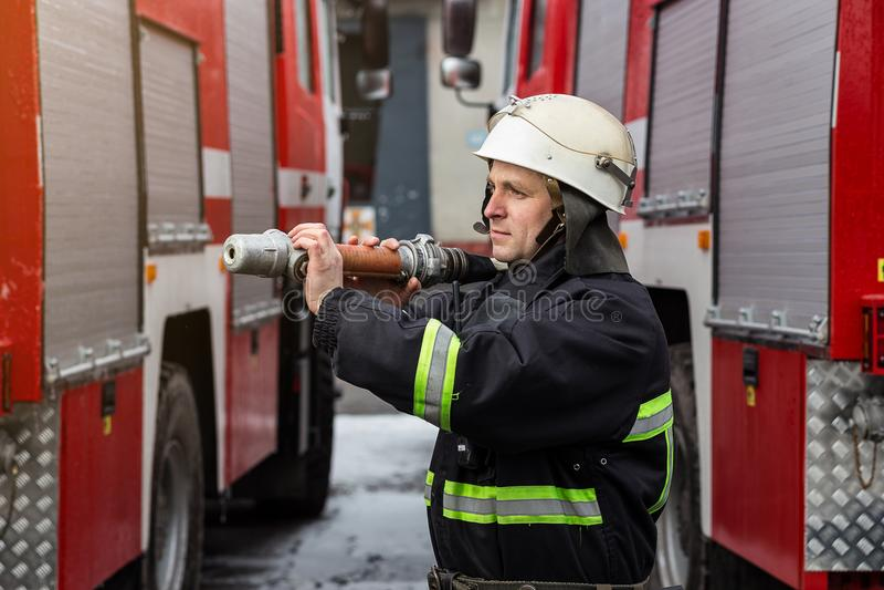 Sapeur-pompier de pompier dans l'action se tenant près d'un firetruck EMER photos stock