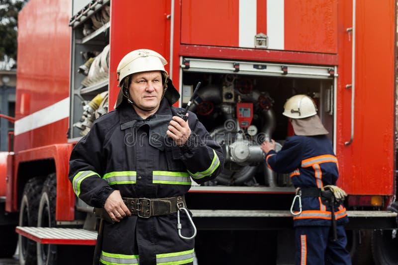 Sapeur-pompier de pompier dans l'action se tenant près d'un firetruck EMER image libre de droits