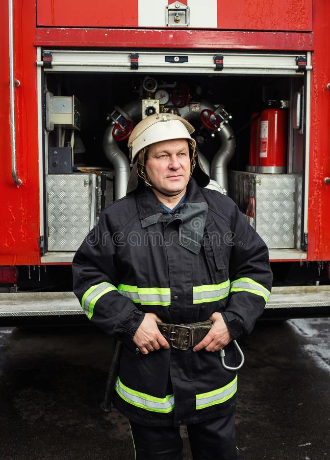 Sapeur-pompier de pompier dans l'action se tenant près d'un firetruck EMER image stock