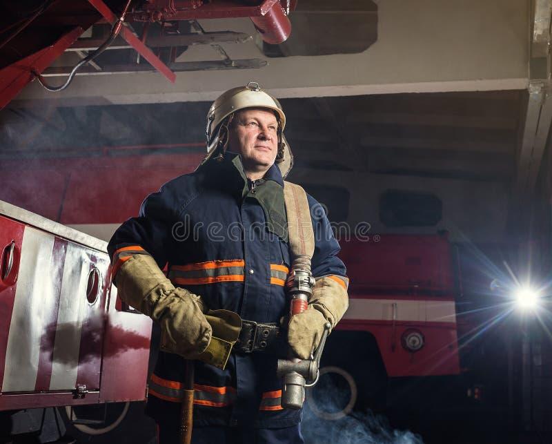 Sapeur-pompier de pompier dans l'action se tenant près d'un firetruck EMER images stock