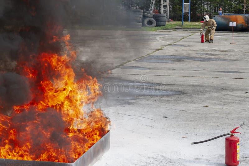 Sapeur-pompier pendant la formation avec un feu énorme dans le brasero photo stock