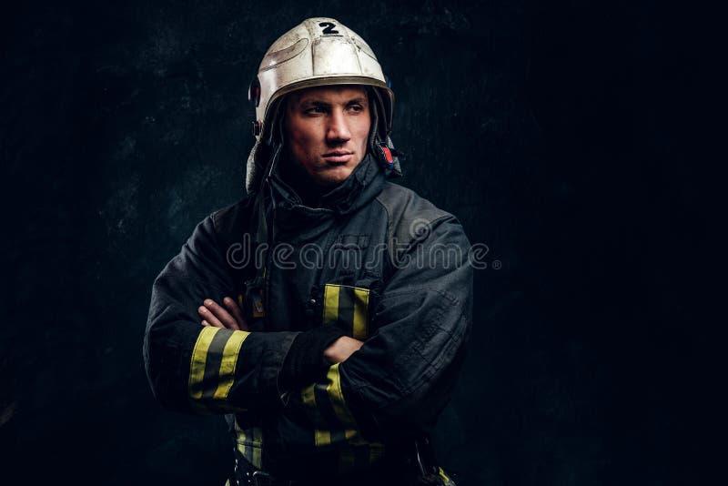Sapeur-pompier viril dans des regards de casque en longueur photographie stock