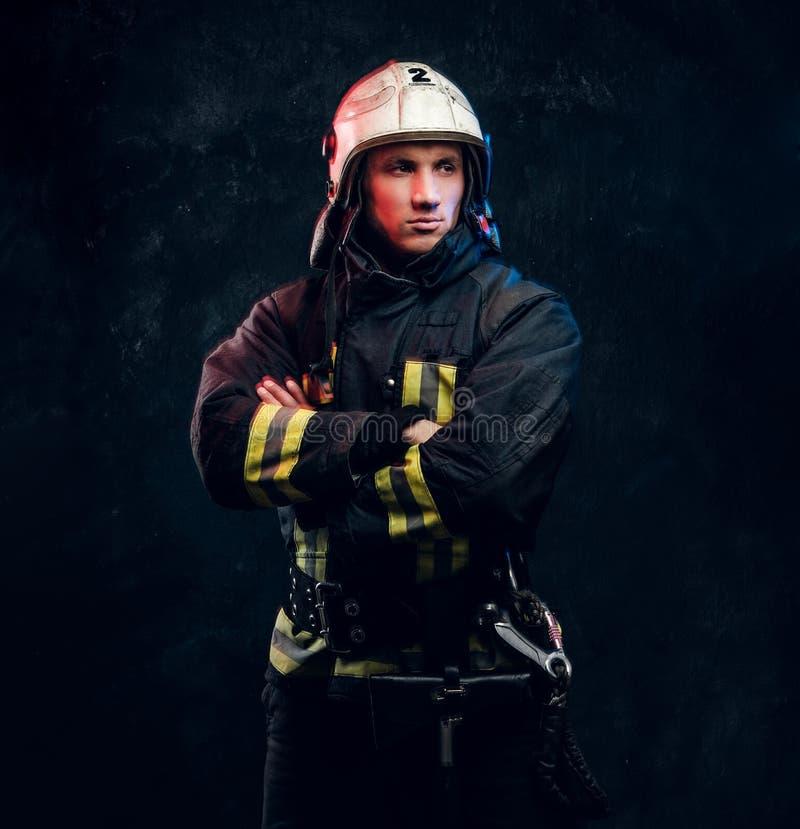 Sapeur-pompier viril dans des regards de casque en longueur images stock