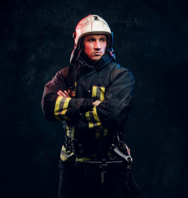 Sapeur-pompier viril dans des regards de casque en longueur image libre de droits