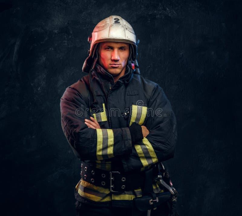 Sapeur-pompier viril dans des regards de casque dans la caméra photo stock