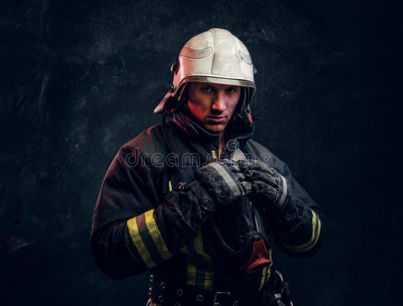 Sapeur-pompier viril dans des regards de casque dans la caméra photographie stock