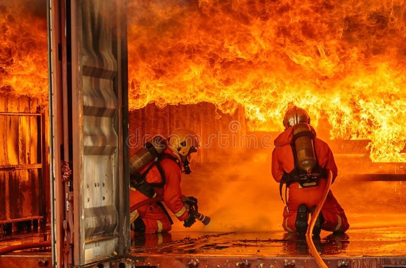 Sapeurs-pompiers combattant un feu, formation de sapeur-pompier image stock