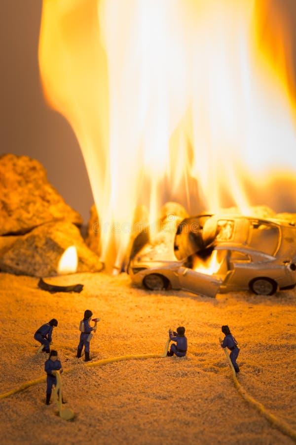 Sapeurs-pompiers miniatures à une scène d'accident de voiture en flammes photographie stock libre de droits