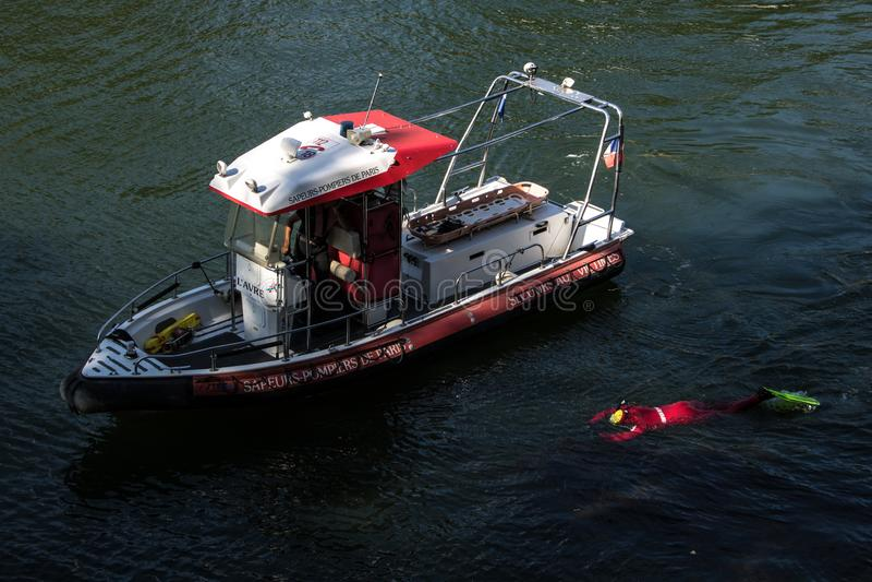 Sapeurs-pompiers parisiens s'exerçant sur la rivière la Seine Un homme dans l'équipement de scaphandre submergé sous l'eau photos stock