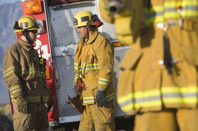Sapeurs-pompiers parlant les uns avec les autres image stock