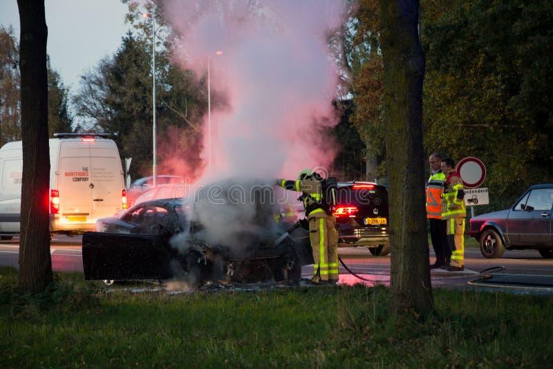 Sapeurs-pompiers près d'une épave de voiture de burn-out photo stock