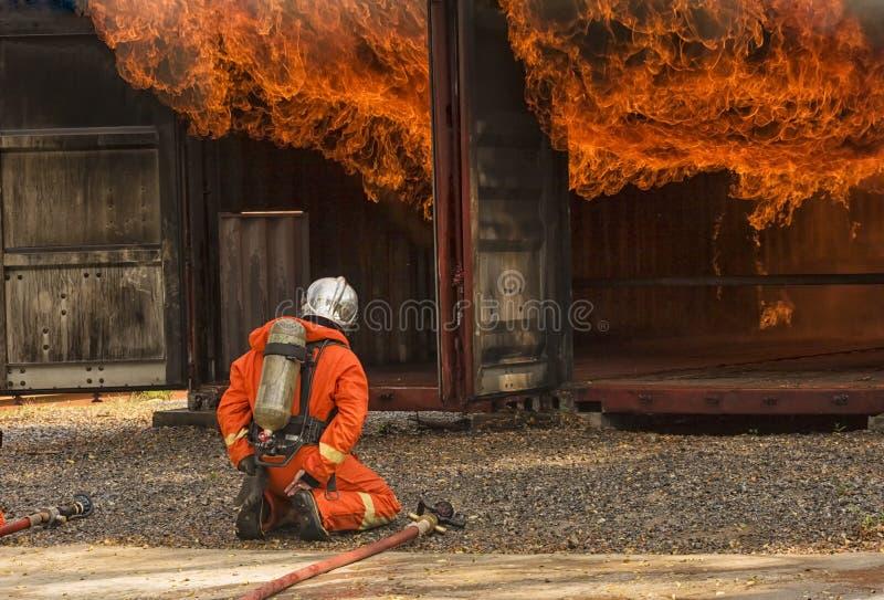 Sapeurs-pompiers pulvérisant l'eau à haute pression pour mettre le feu photographie stock libre de droits