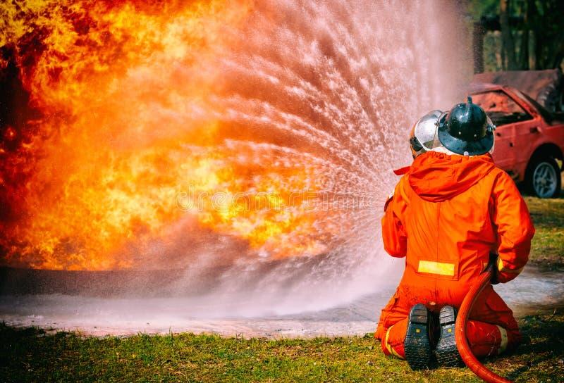 Sapeurs-pompiers pulvérisant l'eau à haute pression pour mettre le feu images libres de droits