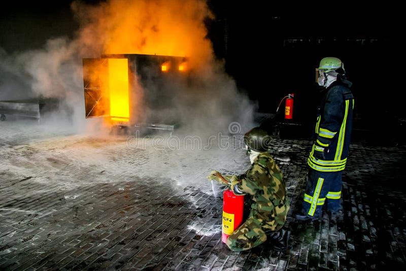 Sapeurs-pompiers s'exerçant pour la lutte contre l'incendie photographie stock libre de droits