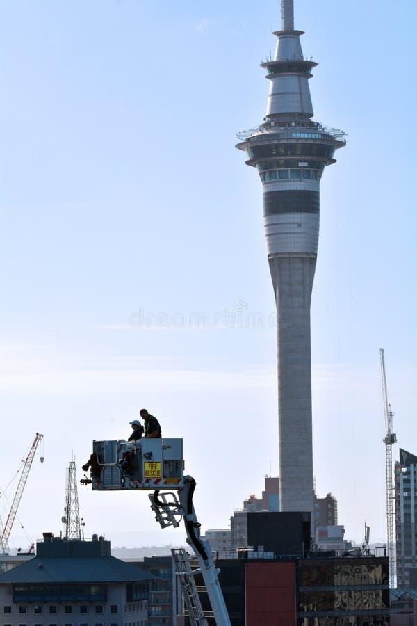 Sapeurs-pompiers sur Crane Platform contre la tour de ciel d'Auckland photos libres de droits
