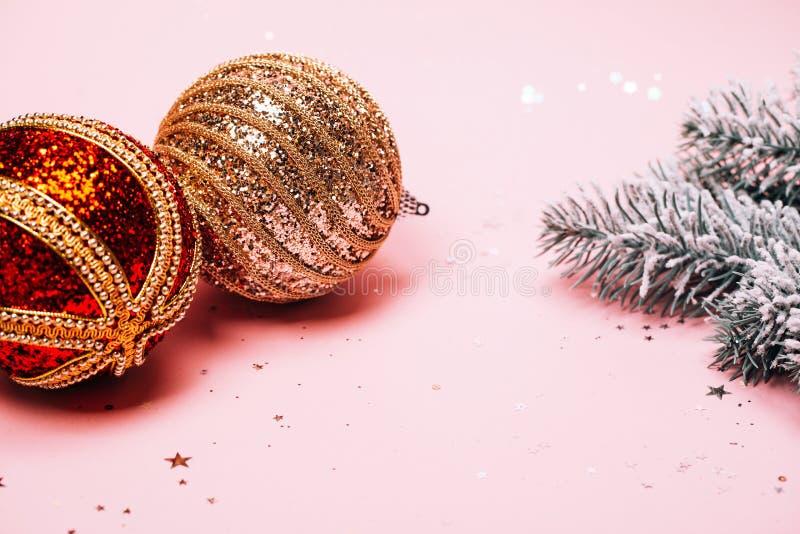 Sapin neigeux de Noël et deux babioles texturisées sur le fond en pastel rose photo libre de droits