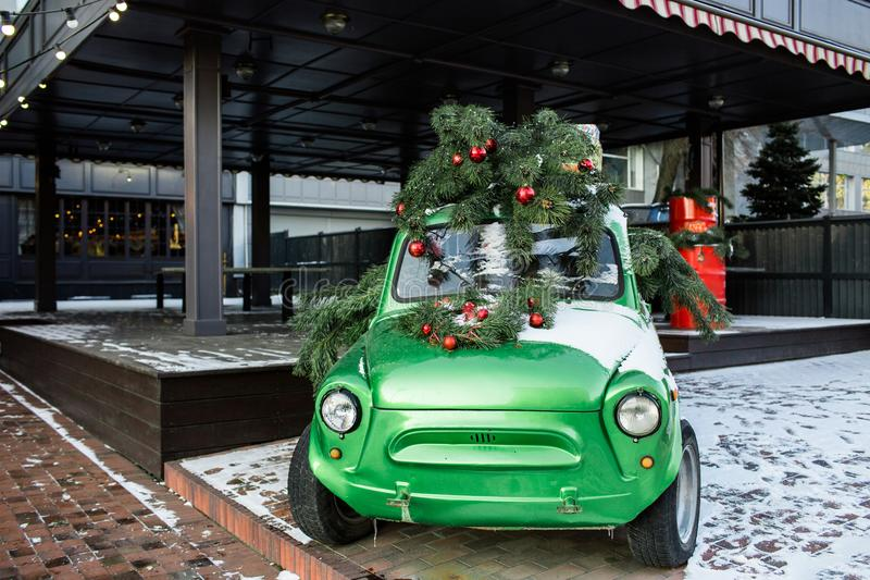 Sapin vert luxuriant sur le toit d'un vert, vieille rétro voiture Pin décoré des boules et des guirlandes rouges de Noël Arbre de photos stock