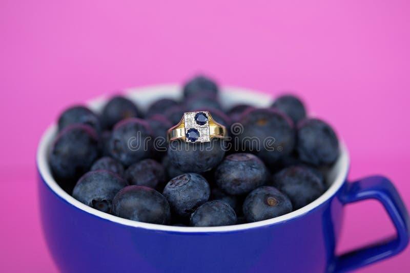 Sapphire And Diamond Gold Ring azul em um copo dos mirtilos foto de stock royalty free