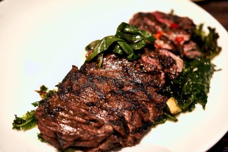 Sappig lapje vlees met geassorteerde groenten op een witte plaat bij een restaurant in Hawa? stock afbeelding