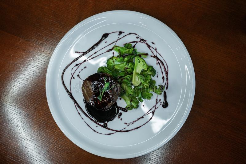 Sappig lapje vlees met gebakken broccoli in een wijnsaus in een restaurant Heerlijke gezonde lunch Close-up Mening van hierboven royalty-vrije stock foto