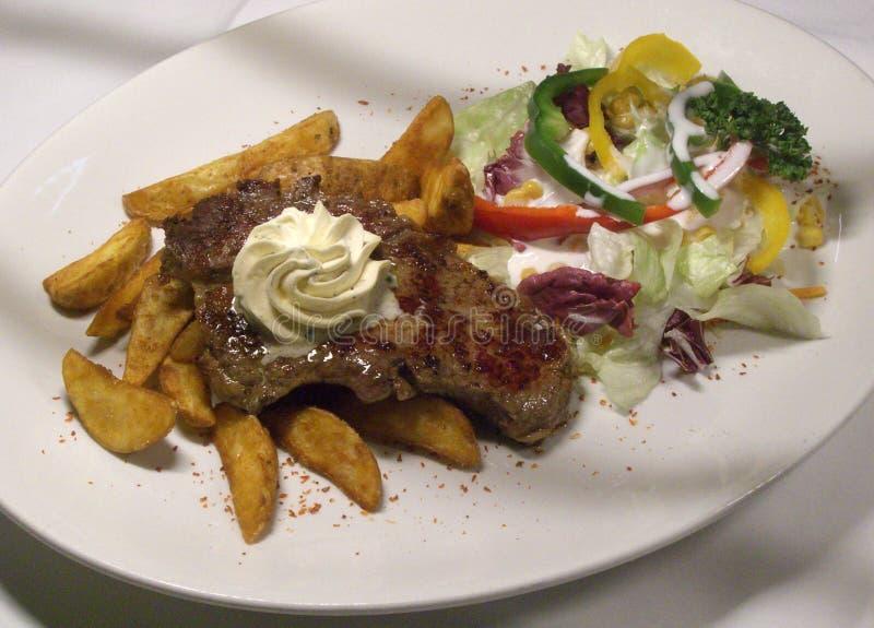 Sappig lapje vlees met kruid boter, gebraden aardappels en gemengde salade royalty-vrije stock foto's
