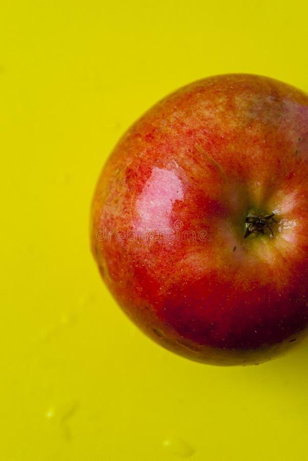 Sappig rood en groen Apple op gele achtergrond stock foto's