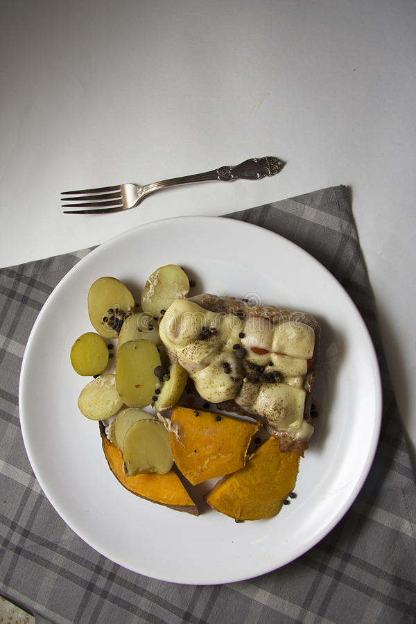 Sappig varkensvlees met kaas en gebakken groenten stock afbeelding