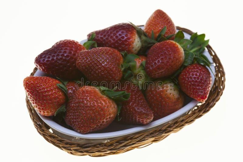 Sappige bessen van rijpe aardbeien in een rieten mand op een witte achtergrond royalty-vrije stock foto's