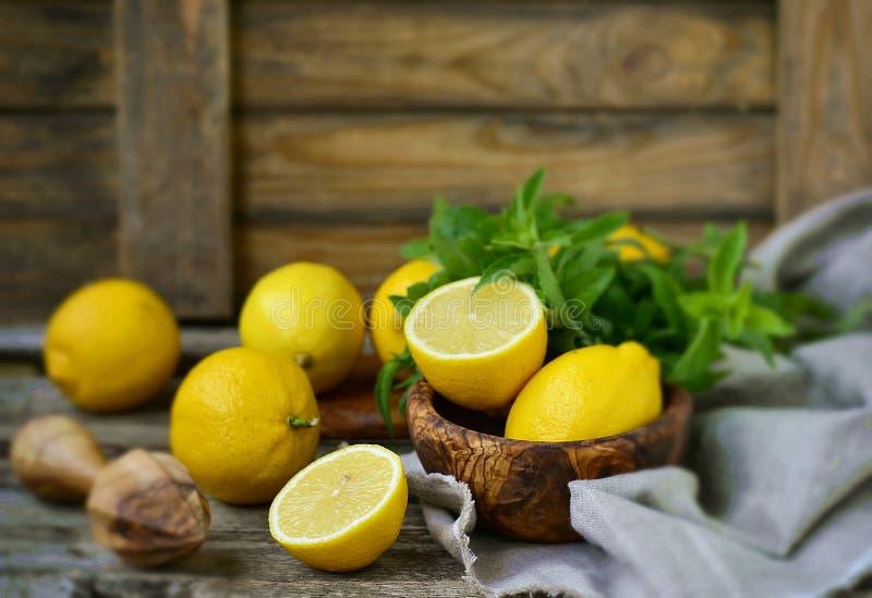 Sappige en rijpe organische citroenen in a en verse munt op een houten achtergrond royalty-vrije stock foto