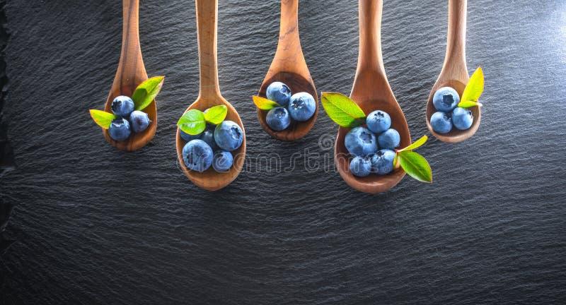 Sappige en verse bosbessen met groene bladeren Concept voor het gezonde eten royalty-vrije stock afbeeldingen
