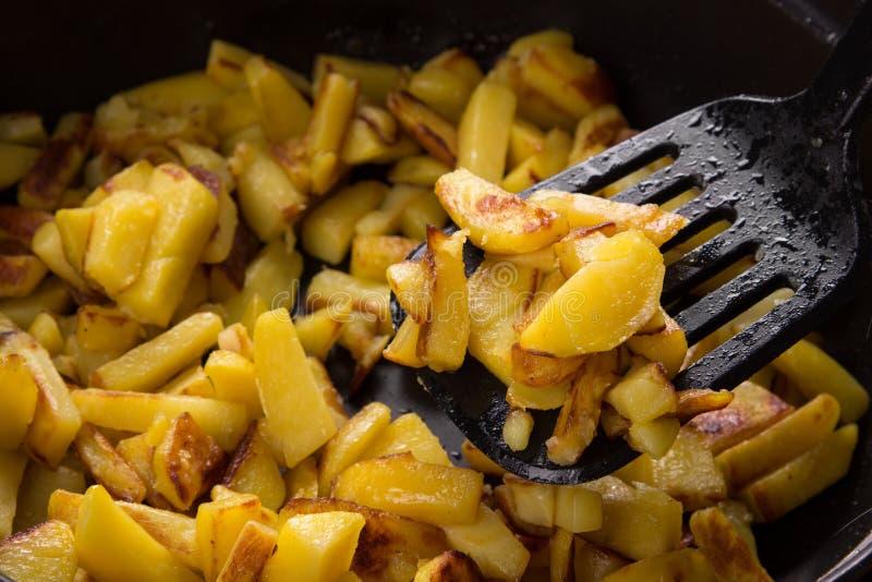 Sappige gebraden aardappels in een pan, eigengemaakte geroosterde aardappels met een knapperige dicht omhoog korst royalty-vrije stock afbeelding