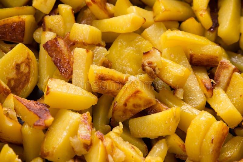 Sappige gebraden aardappels in een pan, eigengemaakte geroosterde aardappels met een knapperige dicht omhoog korst stock afbeelding