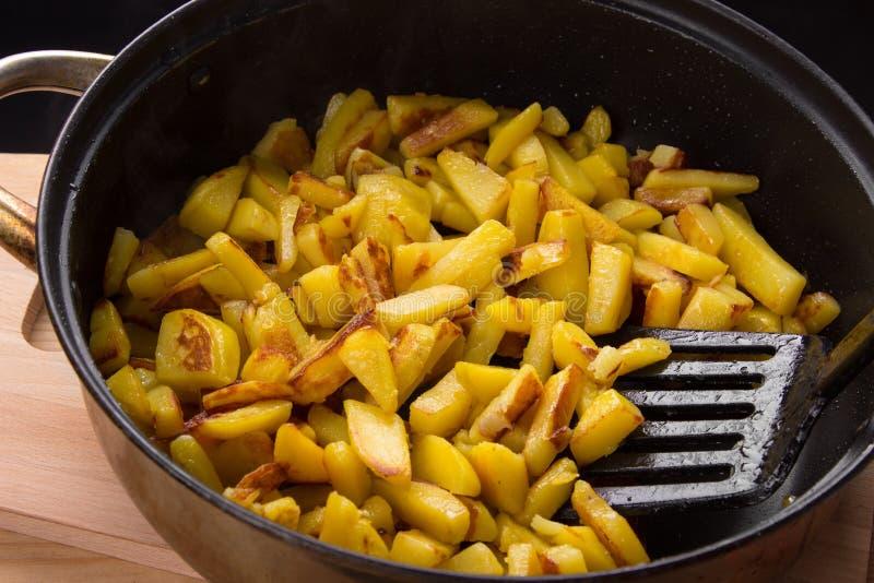 Sappige gebraden aardappels in een pan, eigengemaakte geroosterde aardappels met een knapperige korst royalty-vrije stock afbeeldingen