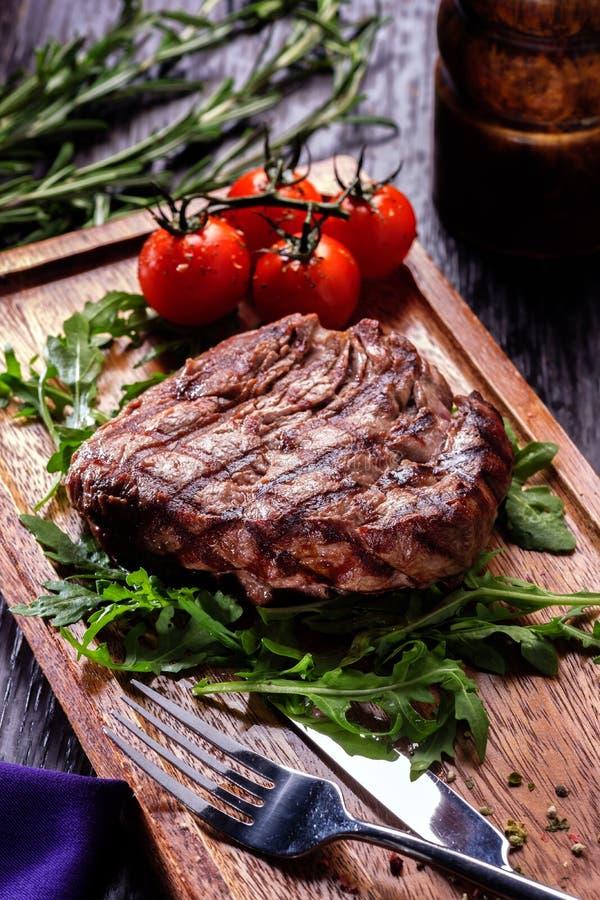 Sappige gedeelten van geroosterd die filetlapje vlees met tomaten wordt gediend en royalty-vrije stock afbeeldingen