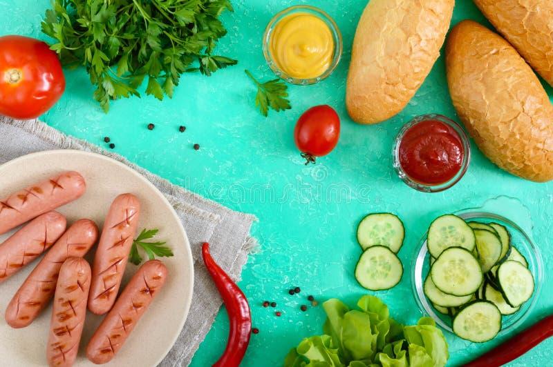 Sappige geroosterde worsten, verse groenten, greens en knapperige broodjes op een heldere achtergrond stock afbeelding