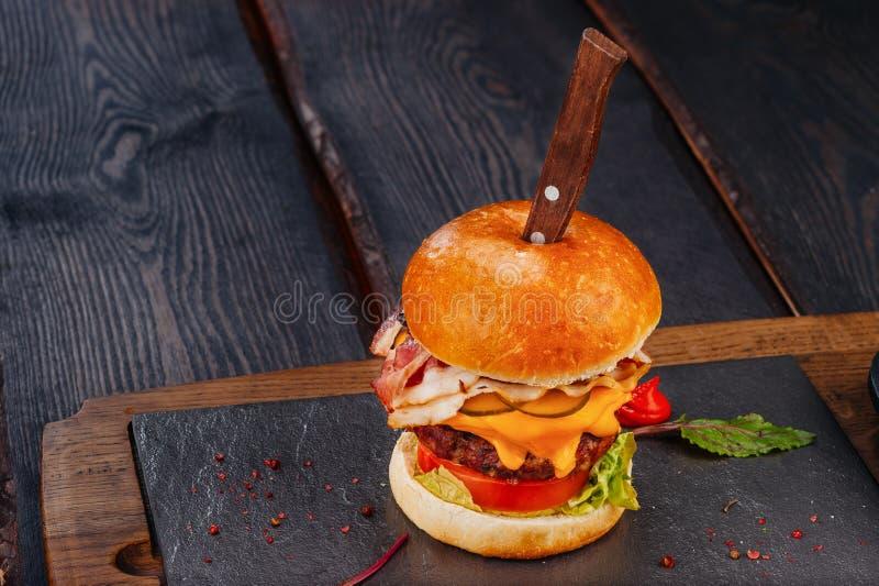 Sappige hamburger met ham, rundvlees en cheddarkaas op rustieke houten raad met mes royalty-vrije stock afbeeldingen