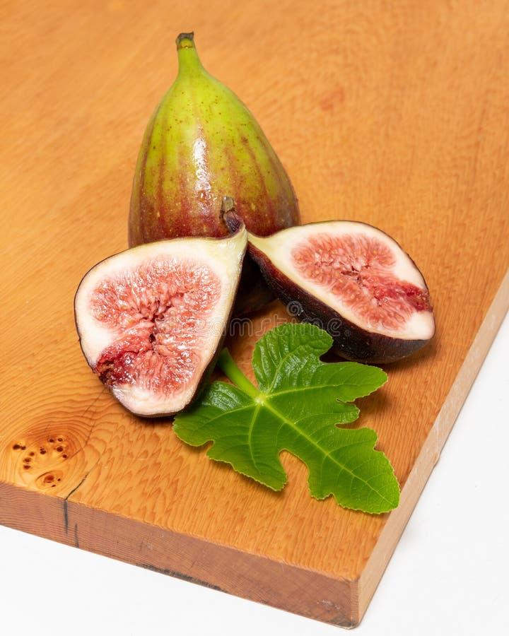 Sappige inlandse fig. onmiddellijk de boom op hakbord met inbegrepen vijgeblad stock fotografie