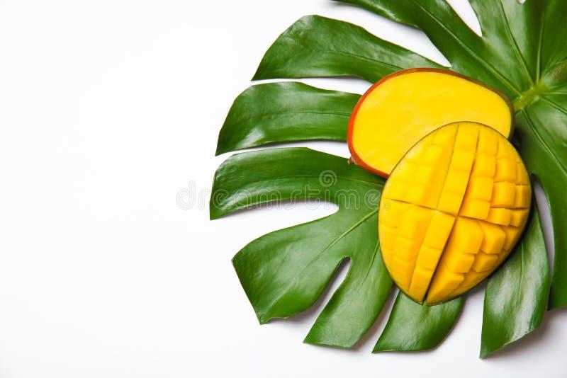 Sappige mango en groen tropisch die blad op witte, hoogste mening wordt geïsoleerd stock fotografie