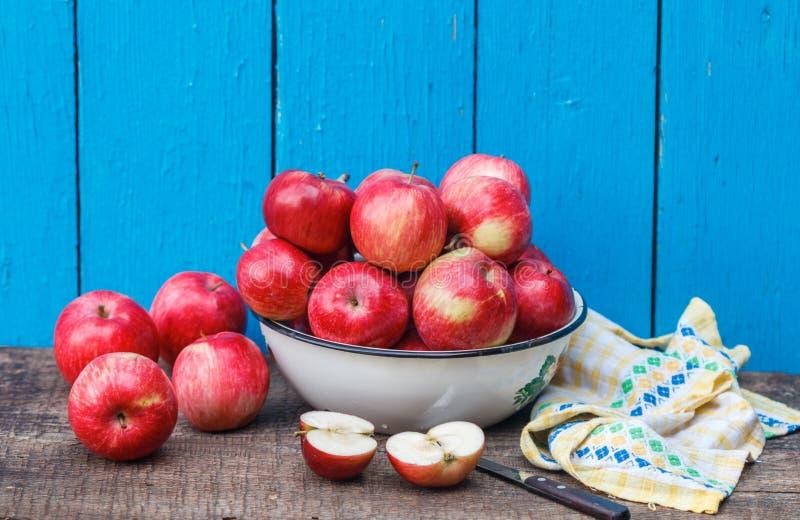 Sappige organische rode rijpe gehele en gesneden appelen op een houten lijst aangaande een blauwe achtergrond stock foto