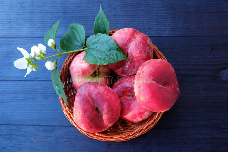 Sappige perziken en bloemen in een mand royalty-vrije stock afbeeldingen