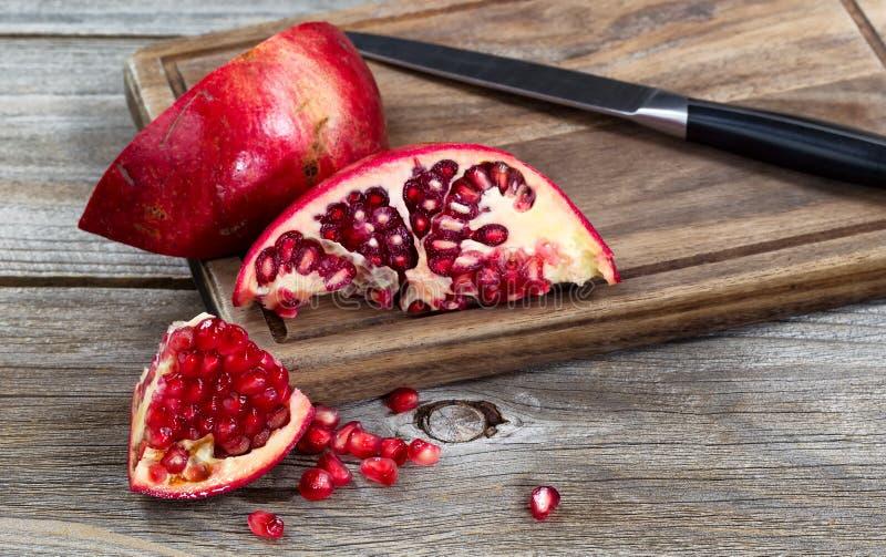 Sappige rijpe granaatappels met mes op uitstekende houten server royalty-vrije stock afbeeldingen