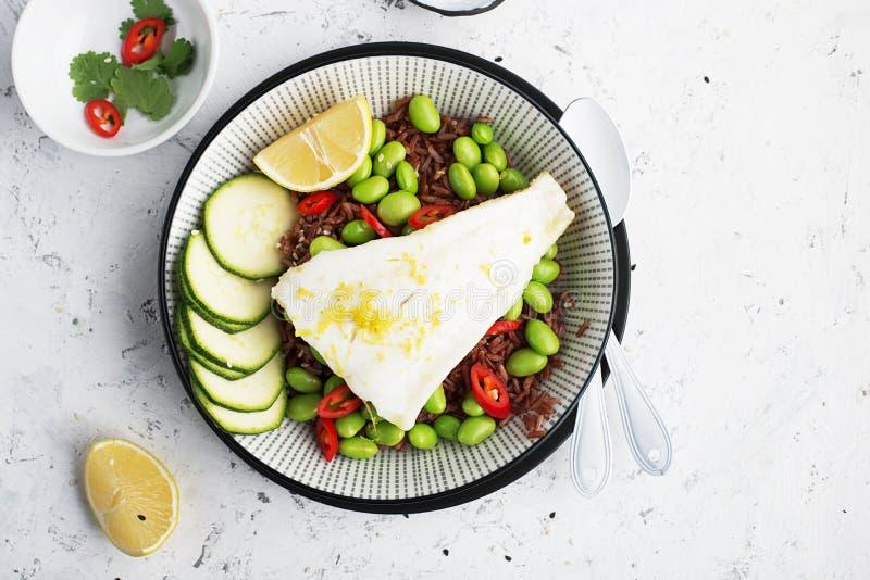 Sappige verse stoom witte overzeese visfilets op een kussen van rode geurige rijst en verse groenten: sojabonen, capsicum royalty-vrije stock foto