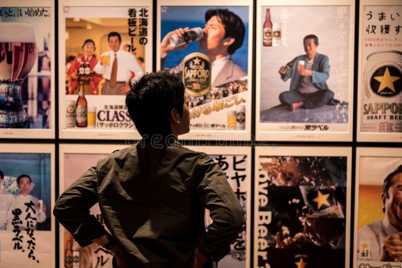 SAPPORO, Japan - MEI 05, 2016: Een mens die Sapporo-bier reclameaffiches bekijken in Sapporo-bier musuem in Sapporo, Hokkaido, Ja stock afbeelding
