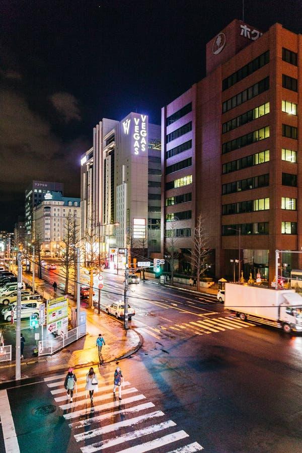 Sapporo nattcityscape med byggnader vänder på ljusen, de rörande bilarna och folket som går i Hokkaido, Japan arkivbilder