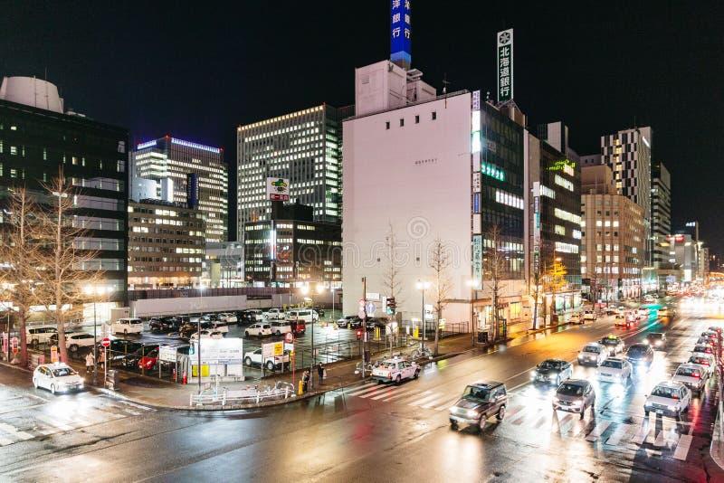 Sapporo nattcityscape med byggnader vänder på ljusen, de rörande bilarna och folket som går i Hokkaido, Japan arkivfoto