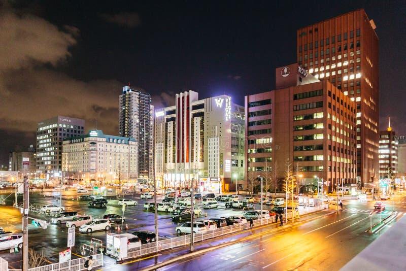 Sapporo nattcityscape med byggnader vänder på ljusen, de rörande bilarna och folket som går i Hokkaido, Japan arkivbild