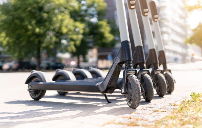 Saqueadores eléctricos de patada en la ciudad. E vehículo de alquiler. Concepto urbano moderno de transporte y tecnología fotografía de archivo libre de regalías