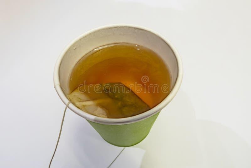 Saquinho de chá ascendente próximo no copo de papel imagem de stock
