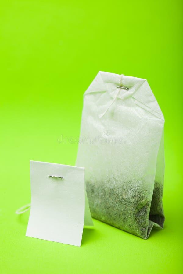 Saquinho de chá com etiqueta vazia Isolado no fundo verde Modelo imagem de stock royalty free