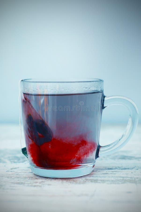 Saquinho de chá vermelho quente do fruto na caneca de vidro no close-up de Gray Wooden Table Imagem vertical toned fotos de stock